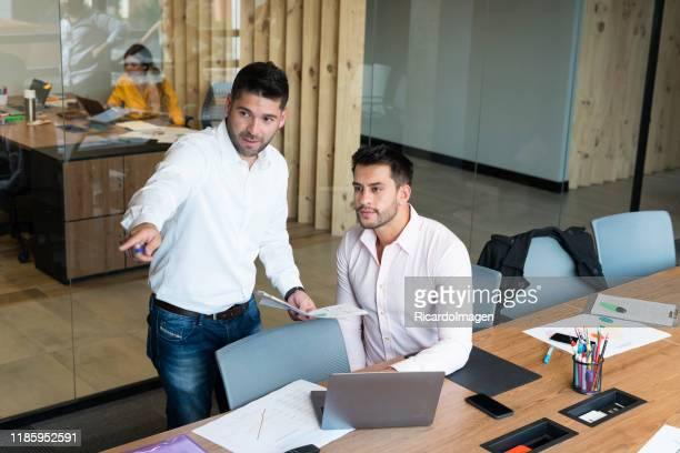 hombres compañeros de trabajo hombres comparten opiniones sobre el trabajo - camisa blanca fotografías e imágenes de stock