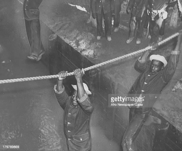 Men cross a 10 ft ditch by holding onto a rope at Aberdeen Proving Ground Aberdeen Maryland September 27 1941