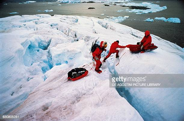 Men crossing a crevasses on the glacier plateau overlooking Prospect point Antarctica
