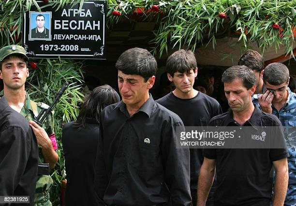 Men cry during the funeral of an Abkhaz soldier who was killed in the remote kodori gorge town of Ghvada while demining a bomb after an armed clash...