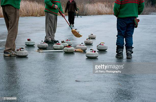 men curling on natural ice - low section stock pictures, royalty-free photos & images