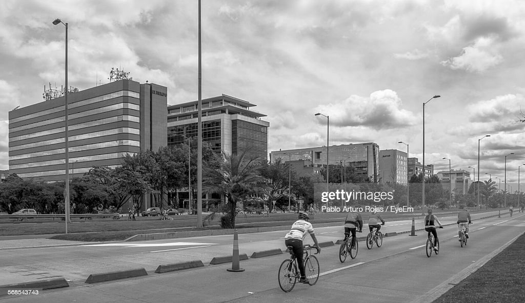 Men Cycling On Road By Buildings Against Cloudy Sky : Stock Photo