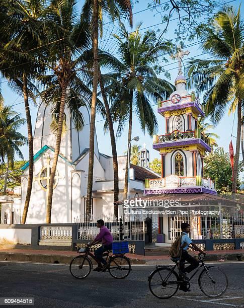 Men cycling past church, Fort Kochi (Cochin), Kerala, India