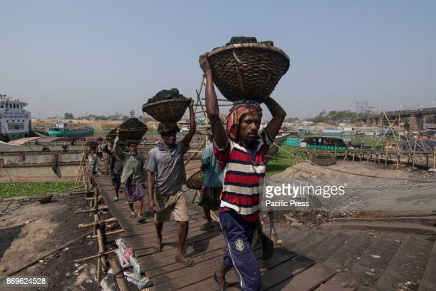 Men daily workers unloading coals from small ships in Turag river capital city Dhaka Bangladesh In the early morning workers starts unloading coals...