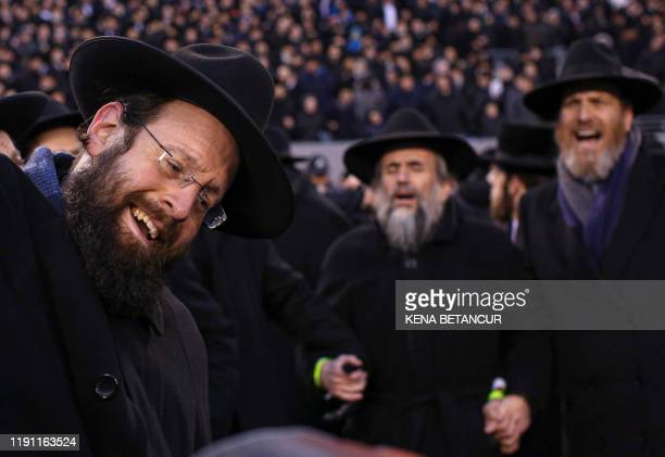 Men dance as they celebrate Siyum HaShas the completion of the reading of the Babylonian Talmud at the MetLife Stadium on January 1 in East...