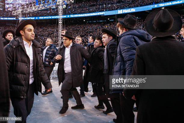 Men dance as they gather with others in MetLife Stadium on January 1 in East Rutherford New Jersey to mark the Siyum HaShas an event that celebrates...