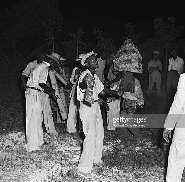 Men dance to the music of vaccines at a party in 1946 in PortauPrince Haiti one of them is wearing a papiermache headdress patterned after those worn...