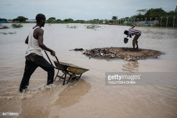 Men dig in a raised patch of earth surrounded by floodwaters after a heavy rainy season downpour as they seek to fill sandbags at the Dadaab refugee...