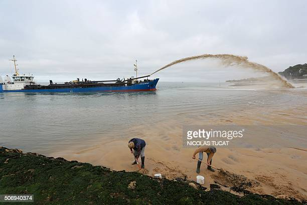 Men dig in the sand as the dredger 'Cotes de Bretagne' shoots sand onto a beach of PylasurMer in La TestedeBuch in Arcachon Bay The boat from...