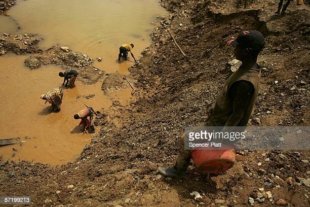 Men dig through dirt and mud while looking for gold at an abandoned industrial mine March 28 2006 in Mongbwalu Congo Thousands of Congolese scrape...