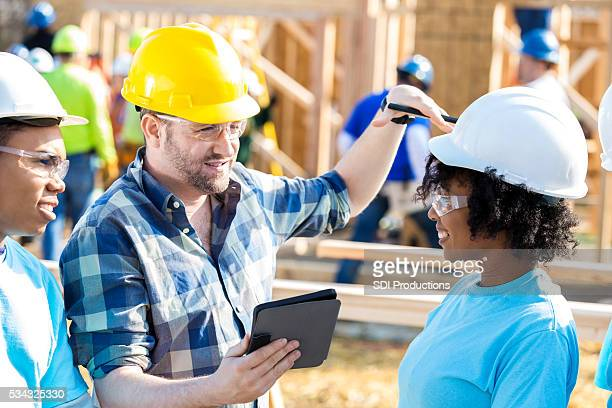 Men discuss building plans with home builder