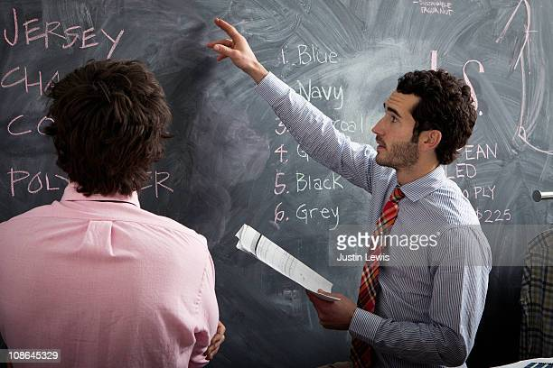 Men discussing business options on blackboard