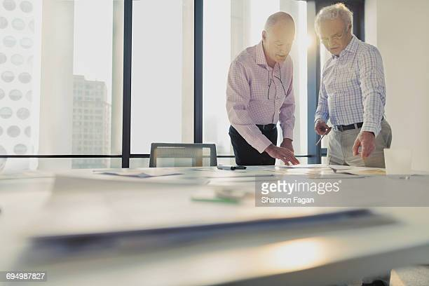 Men discussing layouts on table in office studio