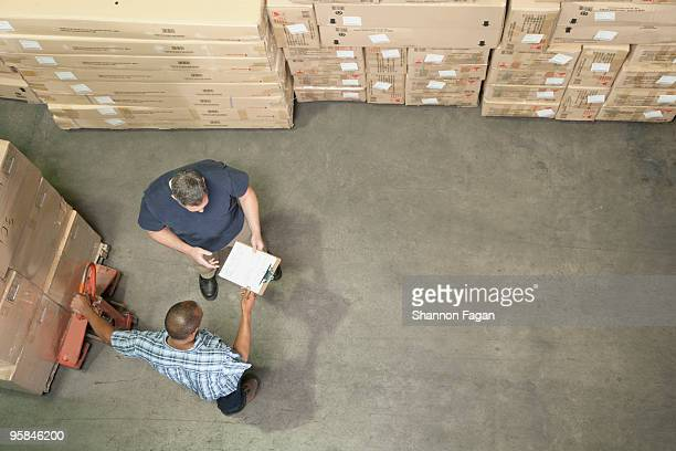 men discussing logistics of an order in warehouse