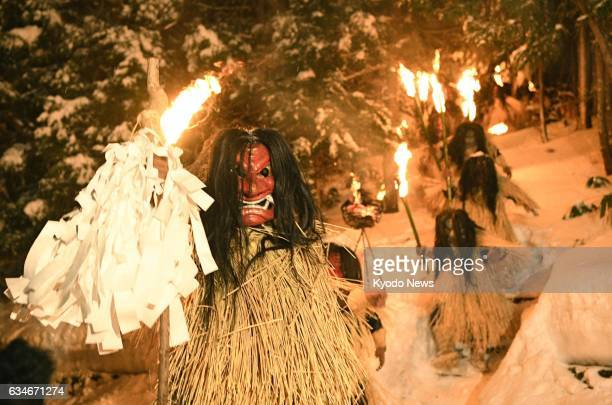 Men disguised as 'Namahage' descend a snowy mountain carrying torches on Feb 10 during the Namahage Sedo Festival at Shinzan Shrine in the...