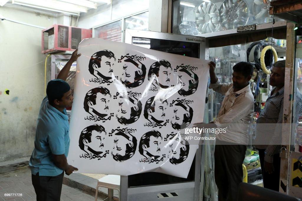 Men display car stickers portraying qatars emir sheikh tamim bin hamad al thani at a shop in the capital doha on june 11 2017