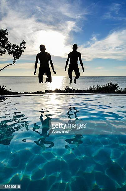Men doing cannonball dives into swimming pool.