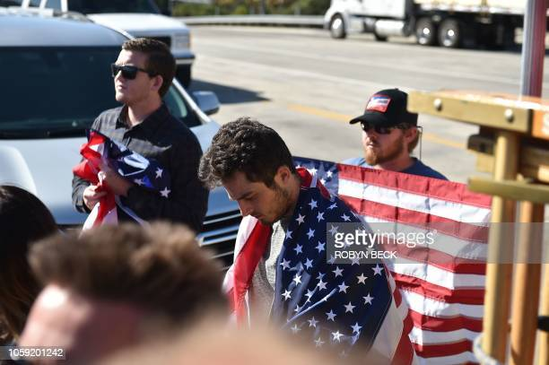 Men drape themselves in US flags as they watch a motorcade procession transporting the body of Sheriff's Sergeant Ron Helus, the first victim named...