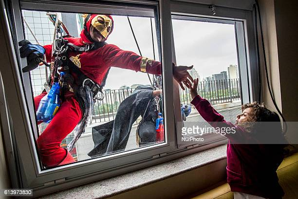 Men dressed as comic book heroes Batman and The Flash prepare to clean the glass facade of Hospital Infantil Sabara before meeting with patients of...
