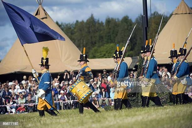 Men dressed as Swedish soldiers march during a reenactment of a battle with mock invading Russian soldiers on the bicentennial of the battle of Savar...