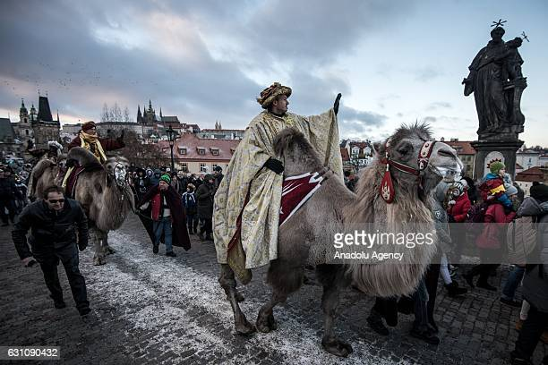 Men dressed as the Three Kings Balthazar Melchior and Gaspar ride camels on the Charles bridge during the Three Kings day in Prague Czech Republic on...