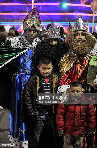 Men dressed as the Three Wise Men pose with children for pictures along Reforma Avenue in Mexico City on January 3 2010 On January 6 Catholics...