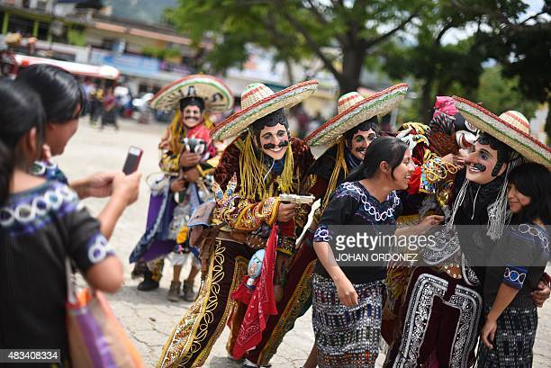 Men dressed for the Dance of the Mexicans pose with indigenous women during the annual fair in honor of the 'Virgen del Transito' in Joyabaj...
