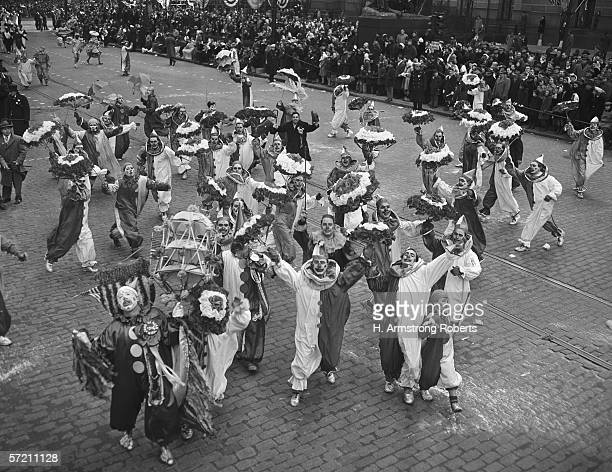 Men dressed in clown suits on street in mummers' parade raising arms and looking up elevated view