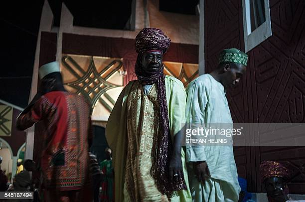 Men dressed in colourful turbans arrive at the Emirate's palace during Waza an event held on the eve of Eid alFitr celebration which marks the end of...