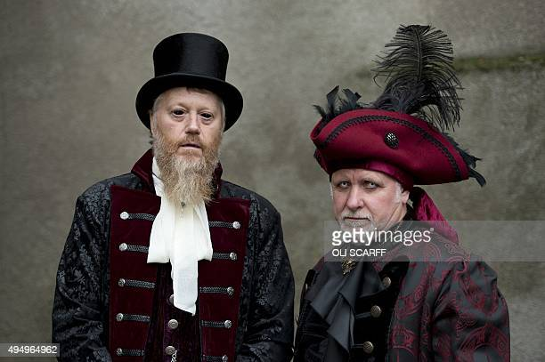 Men dressed in gothic costumes pose during the biannual Whitby Goth Weekend festival in Whitby northern England on October 30 2015 The festival...
