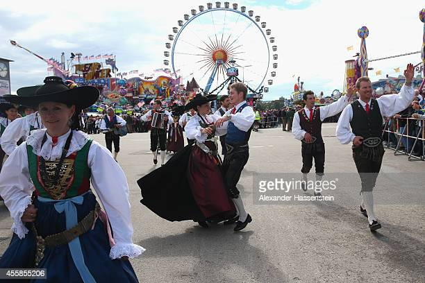 Men dressed in Lederhosen dance with women dressed in Dirndl at the Parade of Costumes and Riflemen on the second day of the 2014 Oktoberfest at...
