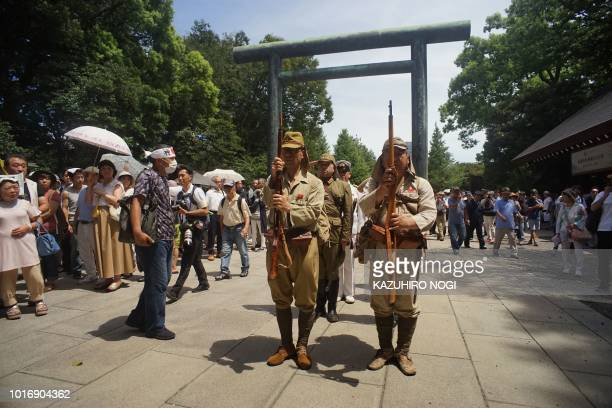 Men dressed in period Japanese Imperial Army and Navy uniforms visit the Yasukuni shrine on the 73rd anniversary of Japan's surrender in World War II...