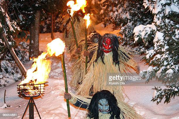 Men dressed in straw clothes and orge masks as Namahage or mountain demons march down from a snow mountain with flaming torches during the Namahage...