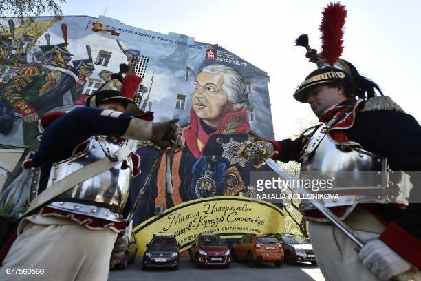 Men dressed in the uniforms of the Imperial Russian army attend the opening of a street art-style painting depicting Russian Field Marshal Mikhail...