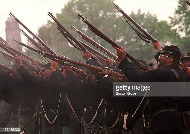 Men dressed in Union Army uniforms reenact a drill as the 54th Massachusetts Volunteer Infantry open fire to commemorate the centennial of a memorial...