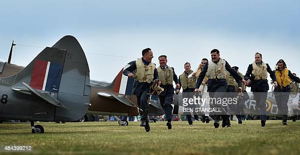 Men dressed in WWII clothing reenact a 'scramble' to awaiting Spitfire and Hurricane aircraft at Biggin Hill airfield in Kent on August 18 2015 World...