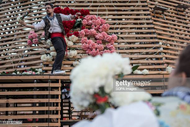 Men dressed up in traditional costume work at the base of a large model of the Virgen de los Desamparados covering it with flowers during Las Fallas...