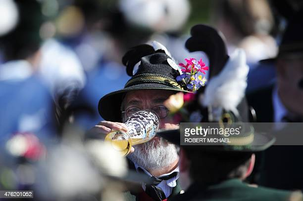 Men dressed with Bavarian traditional regional costumes enjoy a beer before an event with US President and Germany's Chancellor in Kruen near...