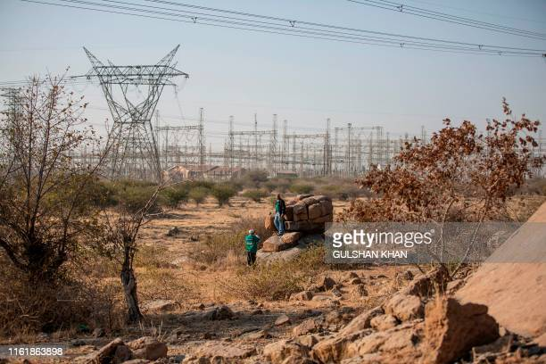 """Men dressed with t-shirts of the """"Association of Mine workers and Construction Union"""" take photos close to the """"koppie"""" and to the Lonmin owned mine,..."""