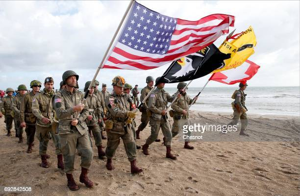 Men dressed with US 101st airborne division military uniforms walk on the beach during commemorations marking the 73th anniversary of DDay the June...