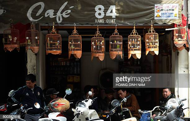 Men drink coffee at a tiny shop decorated with songbird cages in the Old Quarter of Hanoi on December 8 2015 AFP PHOTO / HOANG DINH NAM / AFP / HOANG...