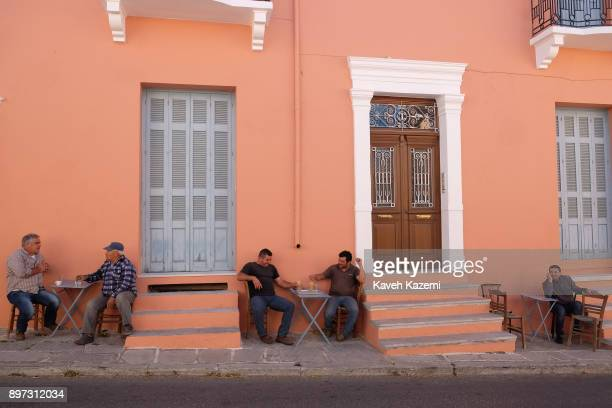 Men drink coffee while sat at tables by a roadside cafe in Halki village in the centre of the island on October 16, 2017 in Naxos, Greece.