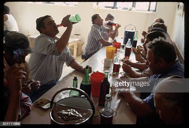 Men drink from bottles of wine on their morning break known as a miranda at the Brac Stone Quarry in Pucisca Croatia Yugoslavia