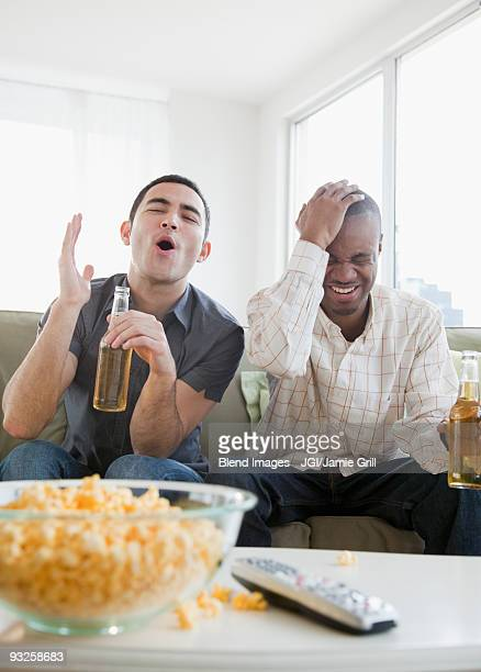 Men drinking beer and watching sports on television