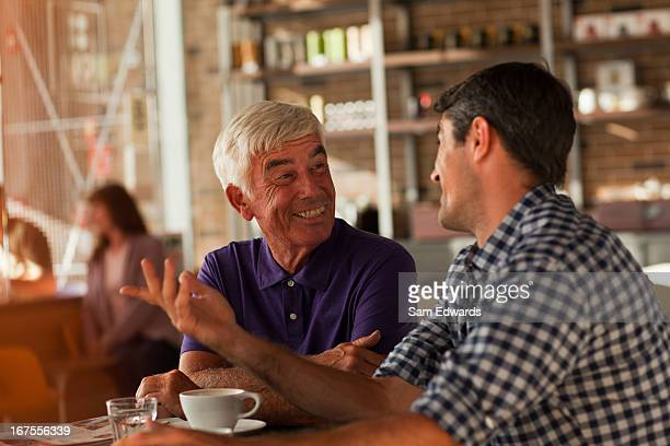 Men drinking coffee together in cafe