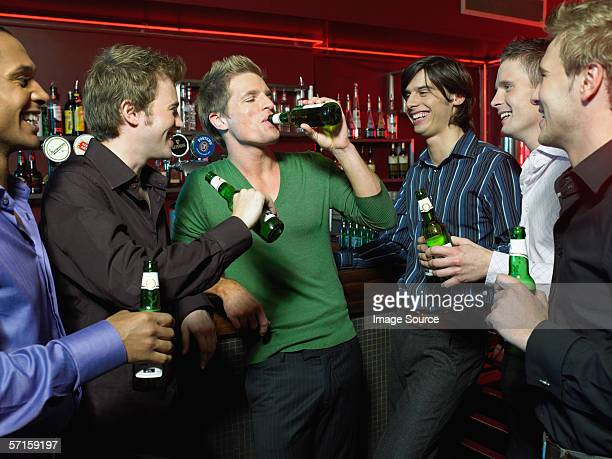 men drinking in a bar - binge drinking stock photos and pictures