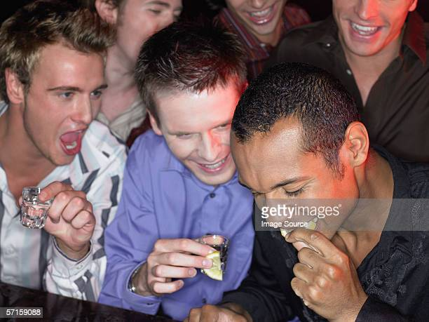 Men drinking shots at a bar
