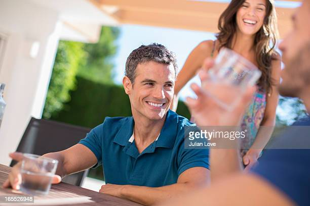 Men drinking water at table outdoors