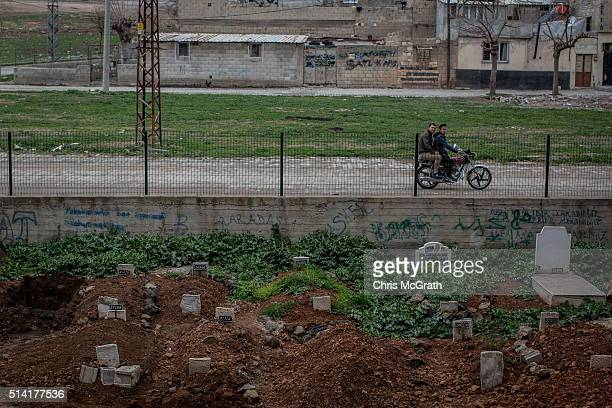 Men drive a motorbike past the small section of the Kilis Cemetery used to bury Syrian refugees on March 4, 2016 in Kilis, Turkey. Kilis a city...