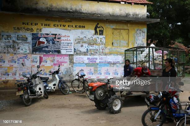 Men drive a vehicle to collect rubbish by a sign that says 'Keep the city clean' in Jaffna Sri Lanka